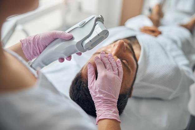 Zbliżenie dłoni kosmetyczki w sterylnych rękawiczkach trzymających urządzenie laserowe i dotykających męskiego czoła