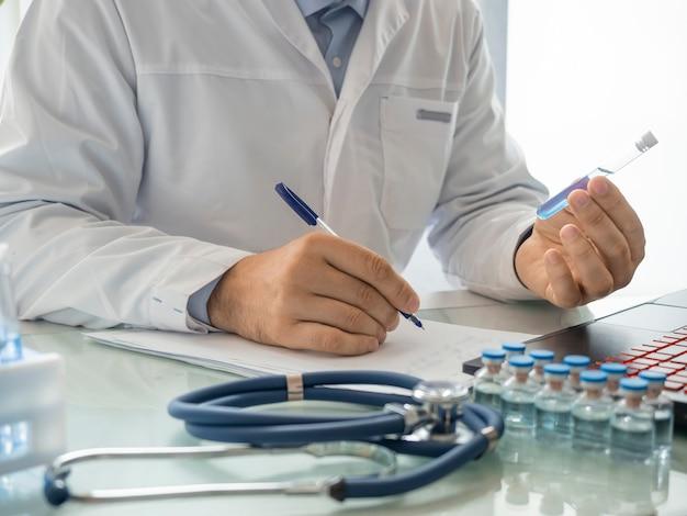 Zbliżenie dłoni lekarza trzymającego probówkę z nowoczesną szczepionką, którą lekarz wprowadza...
