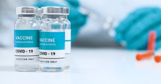 Zbliżenie dłoni lekarza w niebieskich rękawiczkach medycznych z butelką i strzykawką z przezroczystą płynną szczepionką przeciwko koronawirusowi sars-cov-2