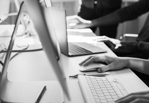 Zbliżenie dłoni ludzi pracujących na komputerach
