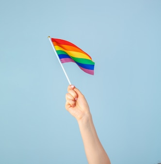 Zbliżenie dłoni macha małą tęczową flagą przed jasnoniebieskim