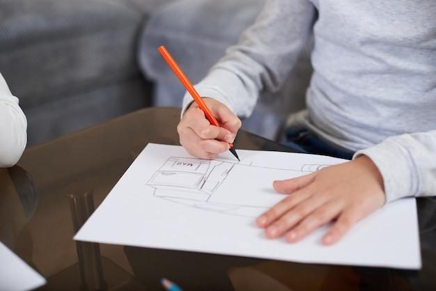 Zbliżenie dłoni małego chłopca trzymającego pomarańczowy drewniany ołówek i rysowanie obrazu na białym papierze