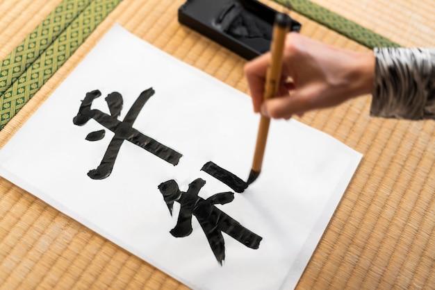 Zbliżenie dłoni malowanie japońskich liter