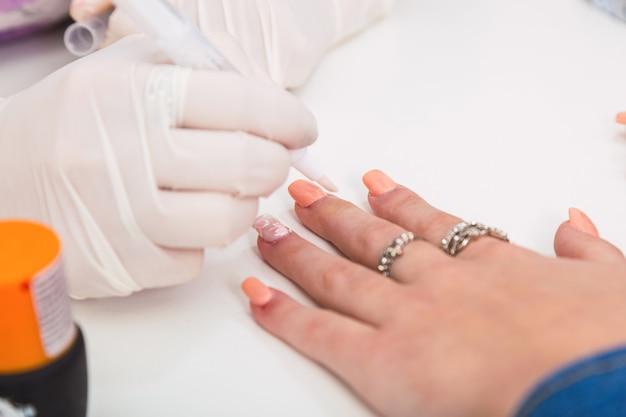 Zbliżenie dłoni manikiurzystki z białymi rękawiczkami do malowania paznokci klienta.