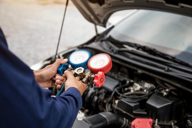 Zbliżenie dłoni mechanika samochodowego używa manometru do napełniania klimatyzatorów samochodowych