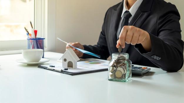 Zbliżenie dłoni męskiego biznesmena za pomocą kalkulatora i robienia notatek z koncepcji raportu księgowego obliczania kosztów i oszczędzania pieniędzy
