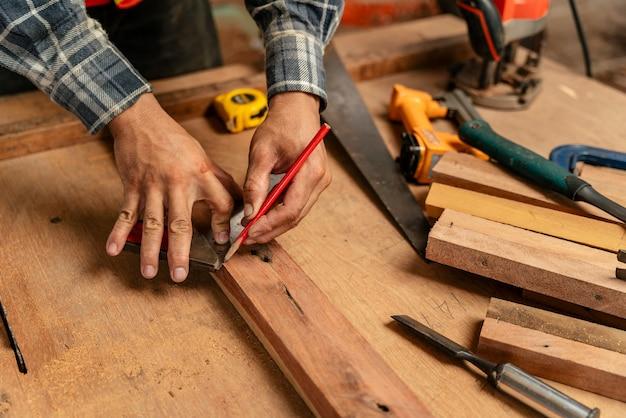 Zbliżenie dłoni męskiego cieśli za pomocą ołówka na kawałku drewna na budowie