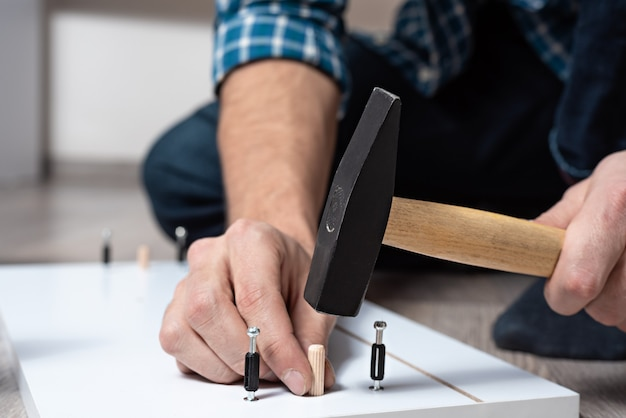 Zbliżenie dłoni mężczyzn z młotkiem zbiera drewniane meble, półki montażowe do skrzyni