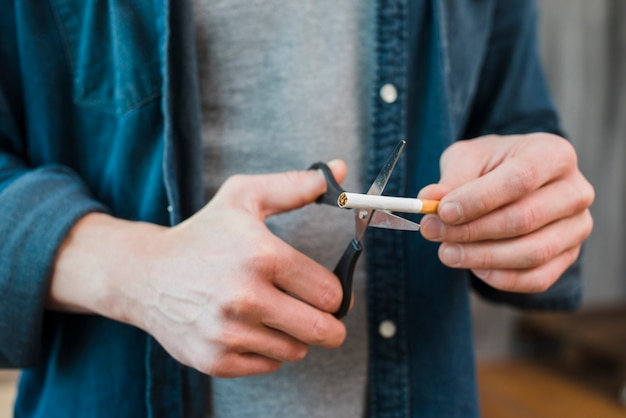 Zbliżenie dłoni mężczyzny cięcia papierosów nożyczkami
