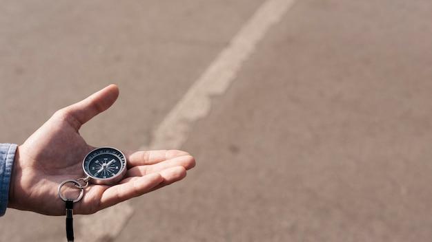 Zbliżenie dłoni mężczyzny gospodarstwa kompas nawigacyjny na ulicy
