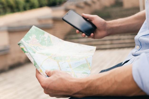 Zbliżenie dłoni mężczyzny gospodarstwa mapę i telefon komórkowy na zewnątrz