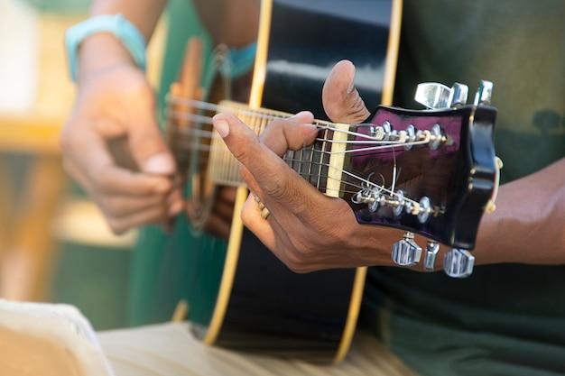Zbliżenie dłoni mężczyzny gry na gitarze akustycznej