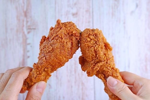 Zbliżenie dłoni mężczyzny i dłoni kobiety brzęk chrupiące smażone udka z kurczaka na drewnianej ścianie