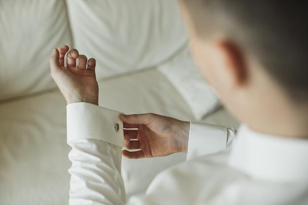 Zbliżenie dłoni mężczyzny, jak nosi białą koszulę i spinki do mankietów