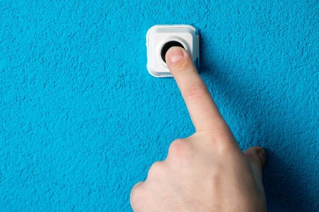 Zbliżenie dłoni mężczyzny naciskając przycisk dzwonka do drzwi