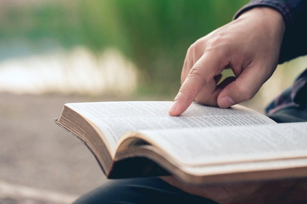 Zbliżenie dłoni mężczyzny podczas czytania biblii poza niedzielne czytania edukacja biblijna