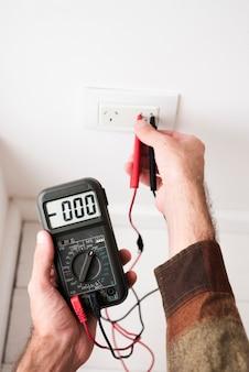 Zbliżenie dłoni mężczyzny podłączania multimetr cyfrowy w wtyczce w domu