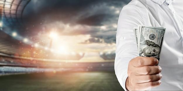Zbliżenie dłoni mężczyzny trzymającego dolary na tle stadionu. pojęcie zakładów sportowych, czerpanie zysków z zakładów, hazard. futbol amerykański.