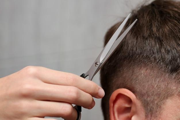 Zbliżenie dłoni mężczyzny trzymającego nożyczki podczas strzyżenia włosów mężczyzny.