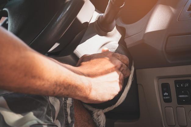 Zbliżenie dłoni mężczyzny z kluczem do uruchomienia silnika, transportu i koncepcji branży ubezpieczeniowej.