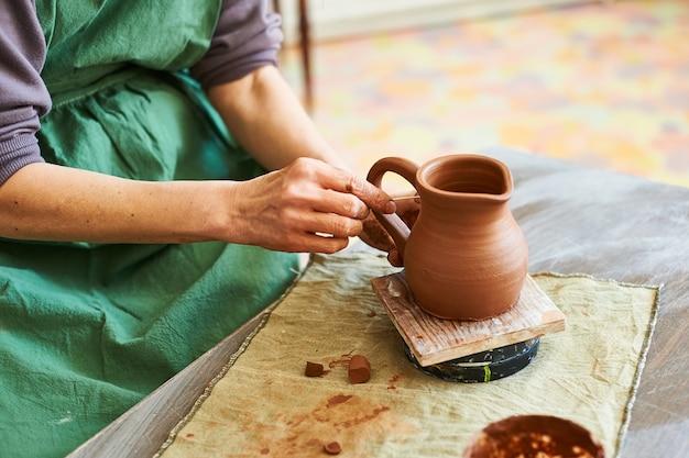 Zbliżenie dłoni mistrza garncarstwa rzeźbi dzban z czerwonej gliny.