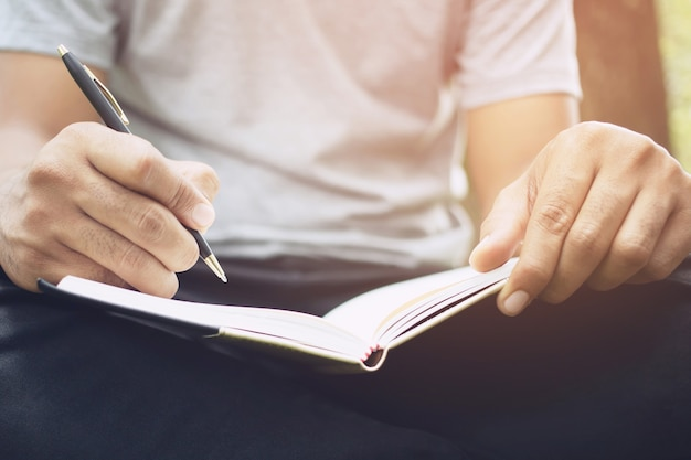 Zbliżenie dłoni młoda kobieta siedzi na marmurowym krześle. używanie pisania piórem notatnik z wykładu zapisuj do książki w publicznym parku.