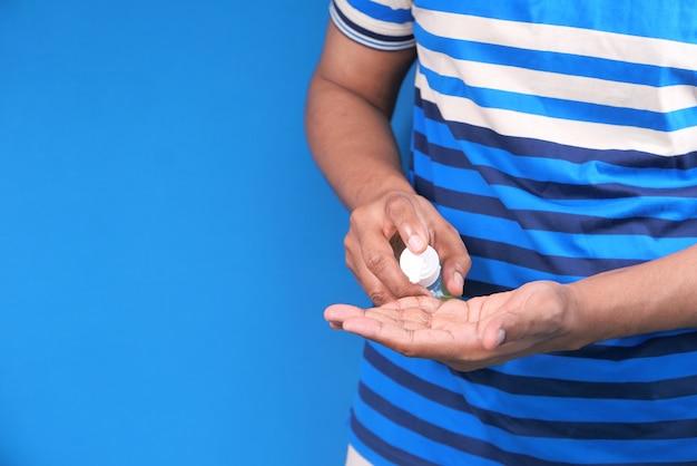 Zbliżenie dłoni młodego człowieka za pomocą żelu dezynfekującego do zapobiegania wirusom.