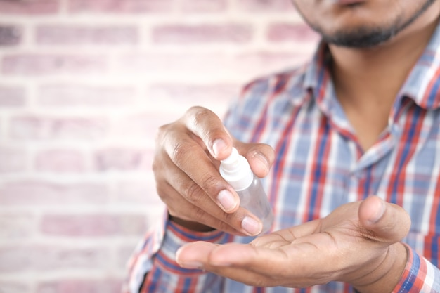 Zbliżenie dłoni młodego mężczyzny za pomocą sprayu do dezynfekcji rąk
