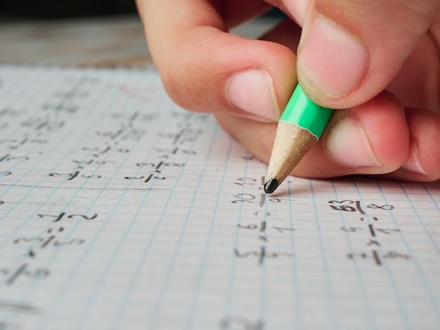 Zbliżenie dłoni młodej dziewczyny odrabiającej lekcje z matematyki, bez twarzy, tylko ręka i ołówek, koncepcja edukacji, spojrzenie z bliska