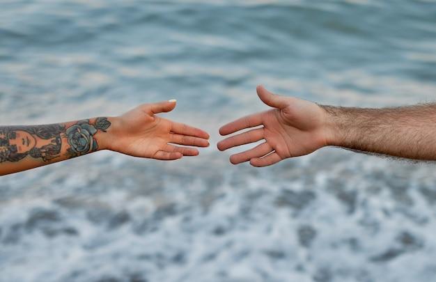 Zbliżenie dłoni młodej pary na tle morza i fal, które rozciągają się ku sobie.