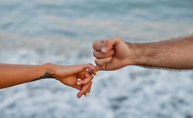 Zbliżenie dłoni młodej pary stojącej nad morzem i falami, trzymającej małe palce w geście akceptacji.