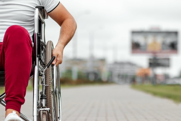 Zbliżenie dłoni na kole wózka inwalidzkiego. pojęcie wózka inwalidzkiego, osoby niepełnosprawnej, pełnego życia, sparaliżowanej, niepełnosprawnej, szczęśliwego życia.