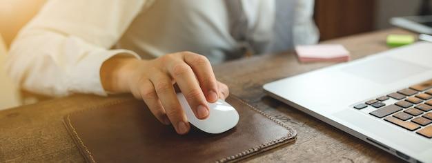Zbliżenie dłoni na myszy komputerowej, mężczyzna pracujący na komputerze