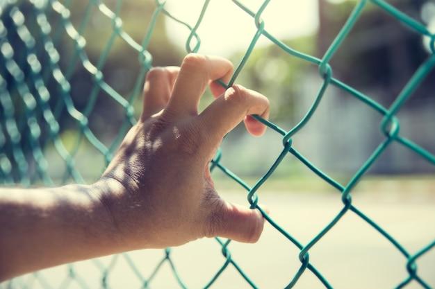 Zbliżenie dłoni na płot łańcucha. ograniczona głębia ostrości