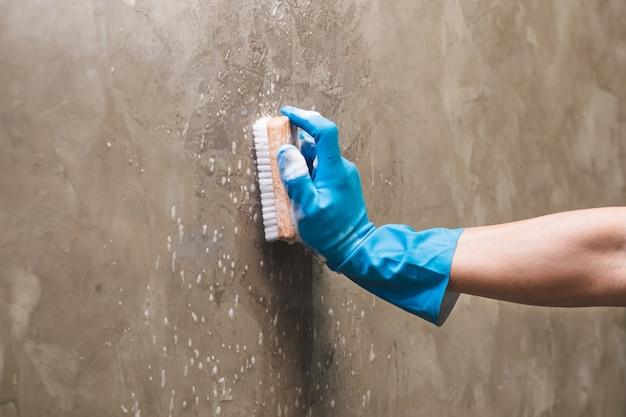 Zbliżenie dłoni na sobie niebieskie gumowe rękawice służy do konwersji czyszczenia szorowania na betonowej ścianie.