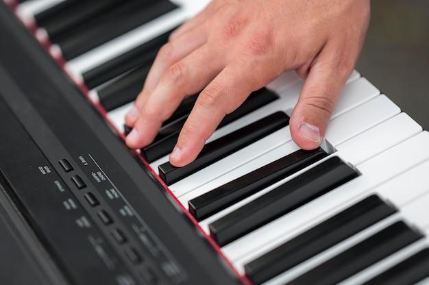 Zbliżenie dłoni na wysokim widoku pianina cyfrowego