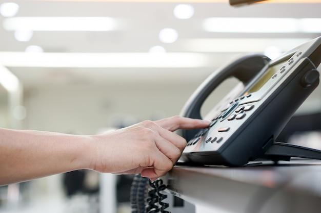 Zbliżenie dłoni naciskając na numer telefonu do wybierania i kontaktu