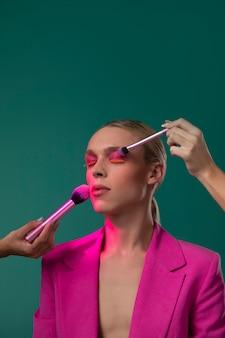 Zbliżenie dłoni nakładając makijaż