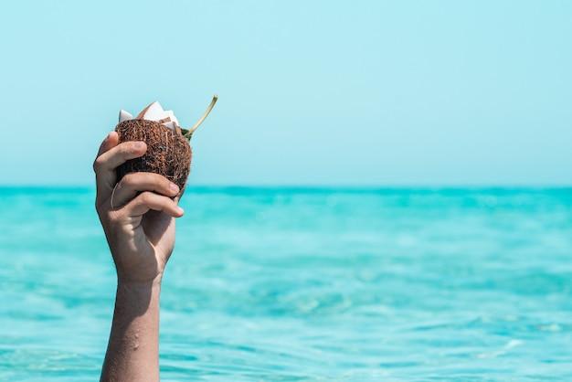 Zbliżenie dłoni nie do poznania osoby trzymającej pół łupin orzecha kokosowego z plastrami na kokosie w nim przeciwko morzu i niebu. latem mokrą dłoń z łupinami orzecha kokosowego. podniesiona ręka trzymająca kokos na tle morza