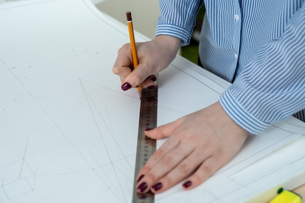 Zbliżenie dłoni ołówkiem i linijką rysuje projekt architektoniczny