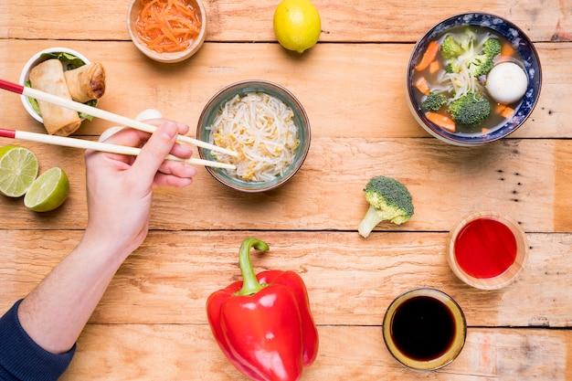 Zbliżenie dłoni osoby jedzenie tajski fasoli kiełki pałeczkami na stole