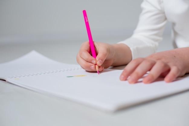 Zbliżenie dłoni osoby rysującej na papierze w albumie z edukacją domową kredką
