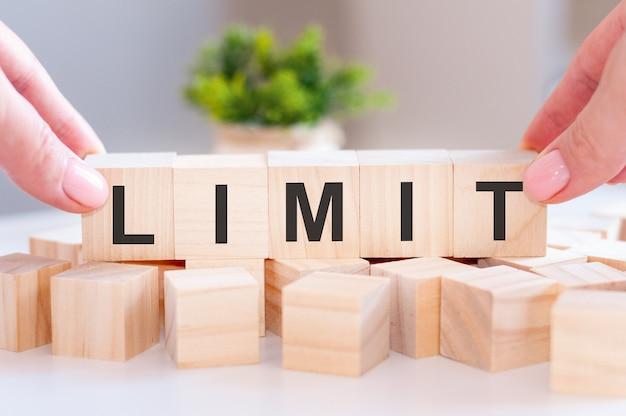 Zbliżenie dłoni osoby trzymającej limit słów na drewnianym stole. pomysł na biznes. selektywna ostrość.