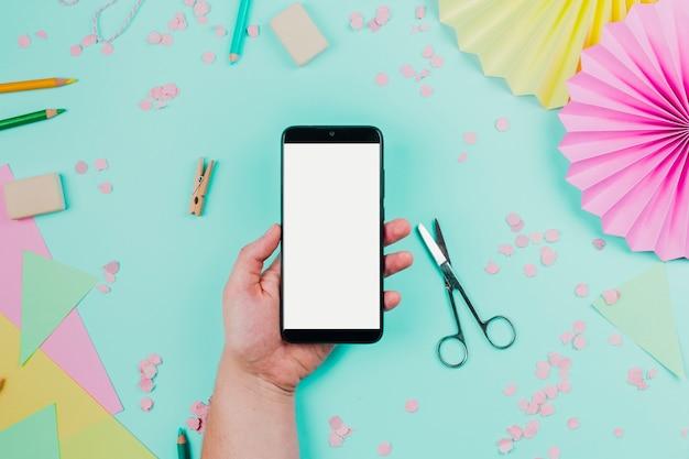 Zbliżenie dłoni osoby trzymającej telefon komórkowy z białym ekranem na tle turkusowy