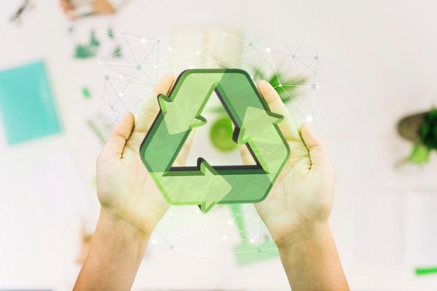 Zbliżenie dłoni osoby z ikoną recyklingu