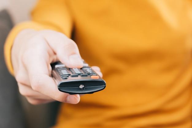 Zbliżenie dłoni osoby z pilotem do telewizora. koncepcja technologii, domu, rozrywki, seriali na streamingu.