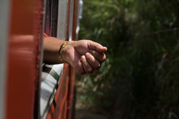 Zbliżenie dłoni osoby ze złotym zegarkiem wokół nadgarstka w pociągu w słońcu