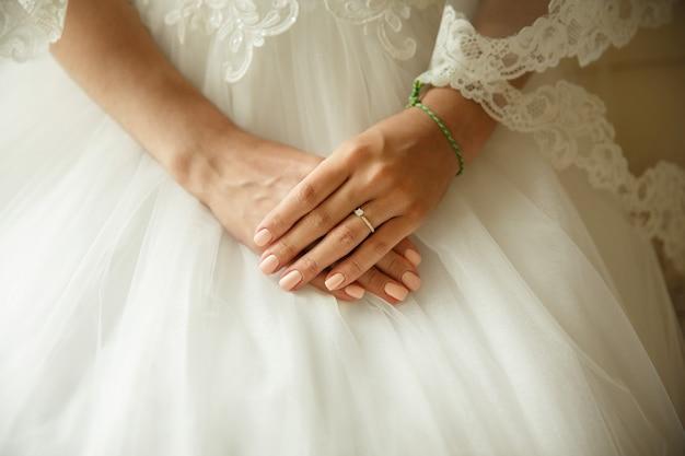 Zbliżenie dłoni panny młodej z pierścionkiem zaręczynowym na białej sukni