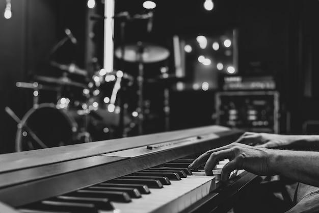 Zbliżenie dłoni pianisty na klawiszach muzycznych na niewyraźne tło.