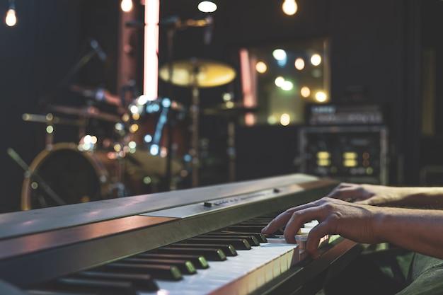 Zbliżenie dłoni pianisty na klawiszach muzycznych z rozmytym tłem.